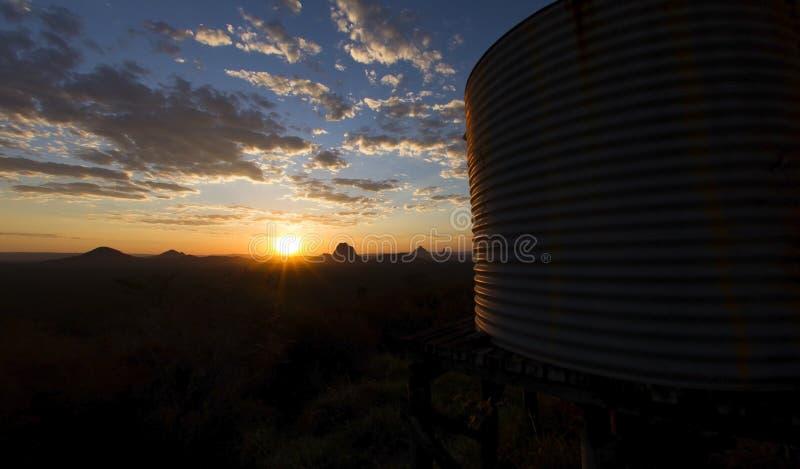 Solnedgång på ett berg bredvid en lantlig vattenbehållare arkivfoto
