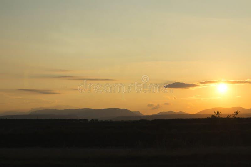 solnedgång på ett fält med berg i backround arkivfoton
