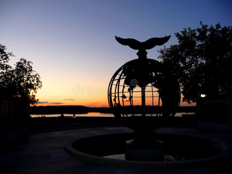 Solnedgång på floden med en örn på en översiktsvärld royaltyfri bild