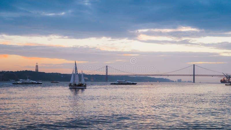 Solnedgång på floden Tagus, Lissabon, Portugal med 25 April Bridge i bakgrund och fartyg royaltyfria bilder