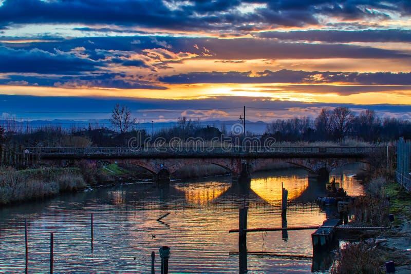 Solnedgång på floden under den forntida järnvägsbron royaltyfria bilder