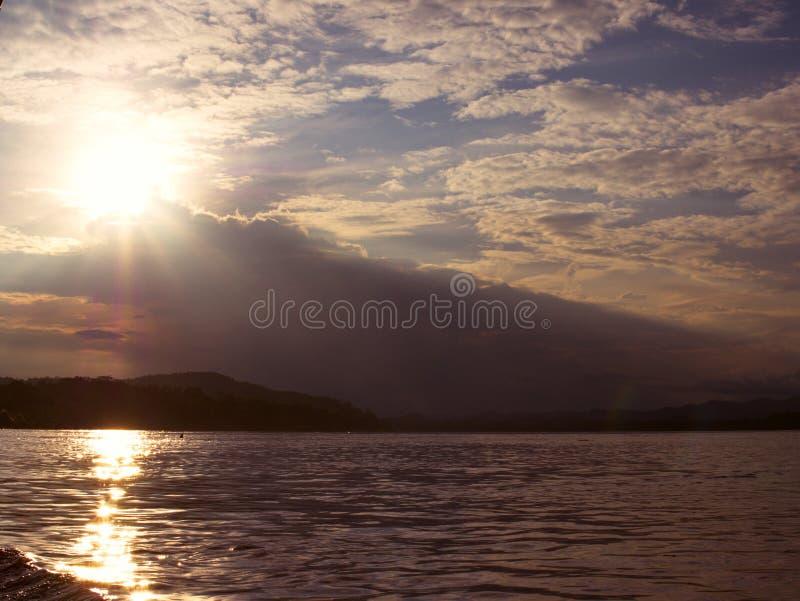 Solnedgång på flodsidan arkivfoto