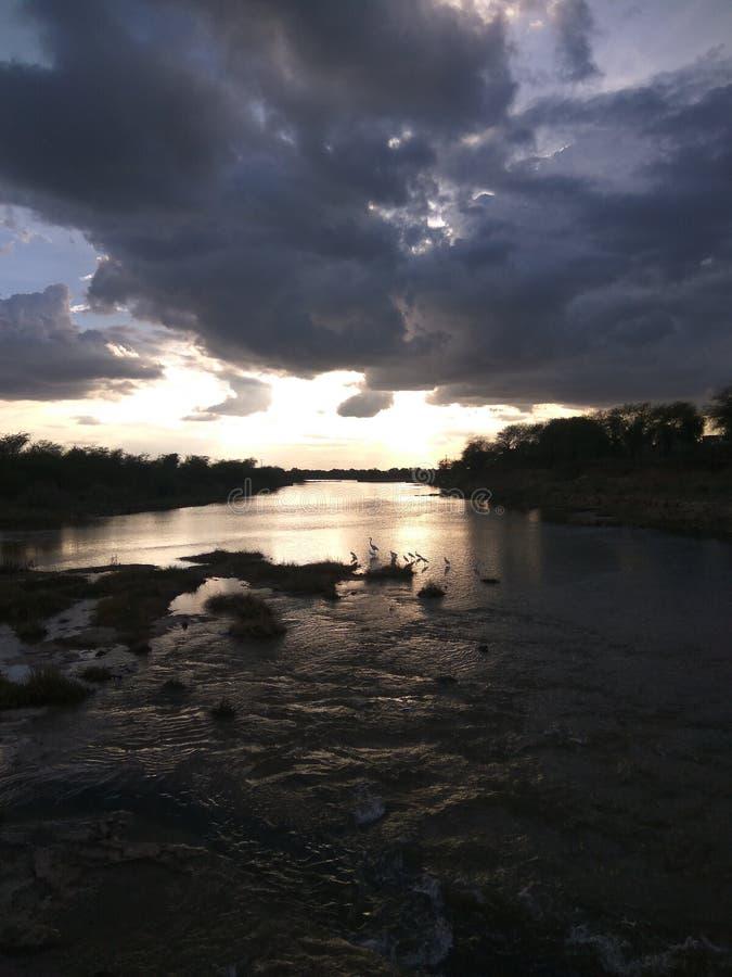 Solnedgång på flodslutet arkivbilder