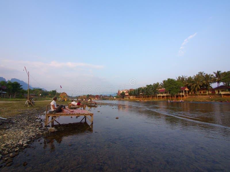 Solnedgång på flodstranden med bergbakgrund, lopp i Vang VI royaltyfria bilder