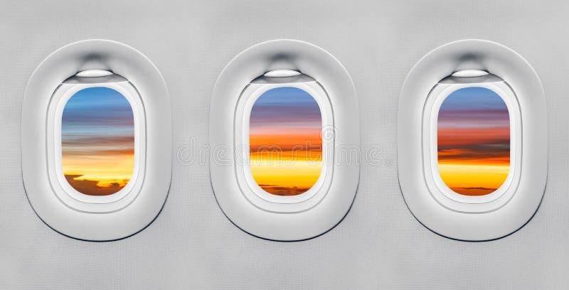 Solnedgång på flygplanfönstret royaltyfria bilder