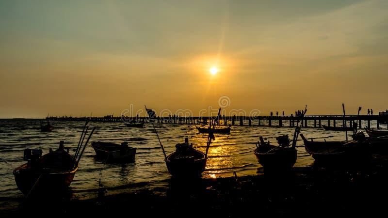 Solnedgång på havet med konturn av fartyget och bryggan arkivfoton