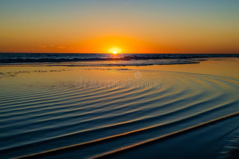 Solnedgång på havet med runda vågor på vatten royaltyfria foton