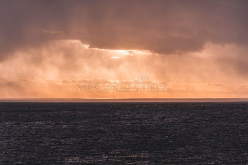 Solnedgång på havet med solljus som kommer till och med regnmolnen, Finland royaltyfri foto
