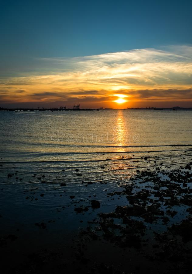 Solnedgång på havet med stenen och vågen arkivfoto