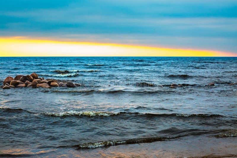 Solnedgång på havet Vågor och blått vatten arkivfoto
