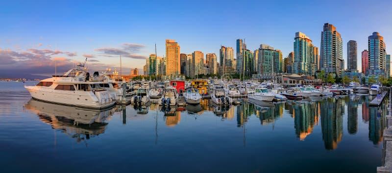 Solnedgång på kolhamnen i Vancouver British Columbia med i stadens centrum byggnadsfartyg och reflexioner i vattnet arkivfoton