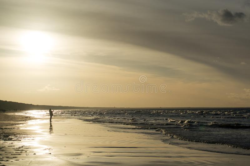 Solnedgång på kusten med folk arkivbild