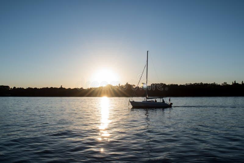 Solnedgång på laken segling royaltyfri foto