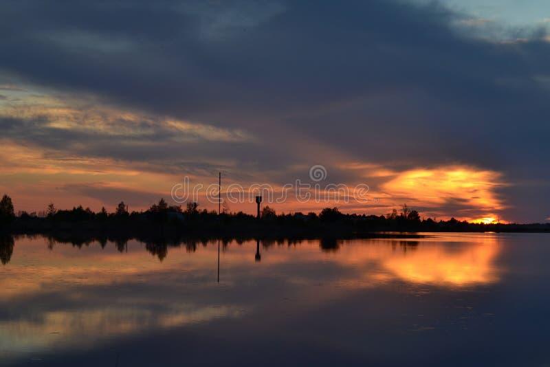 Solnedgång på molnig himmel över sjön royaltyfri bild