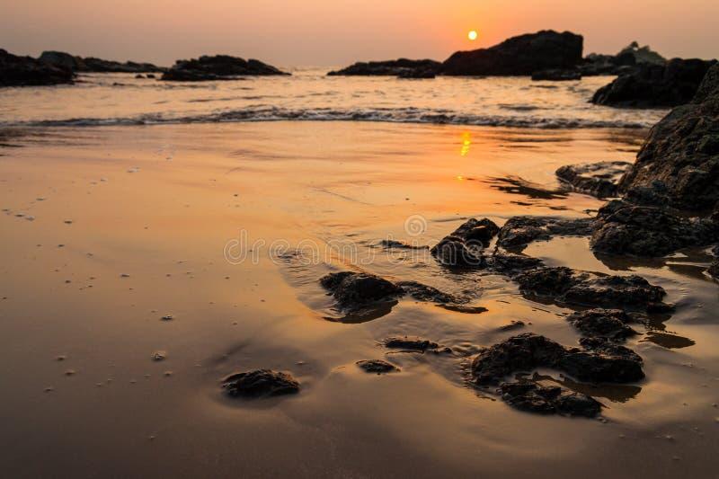 Solnedgång på om-stranden Indien arkivbilder
