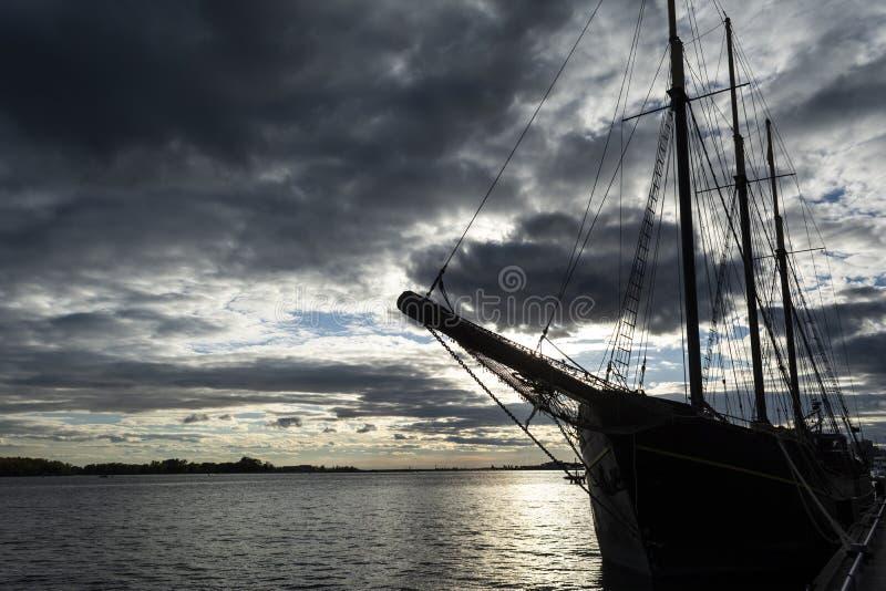 Solnedgång på Ontario sjön med högväxt skeppanseende på marina royaltyfri bild