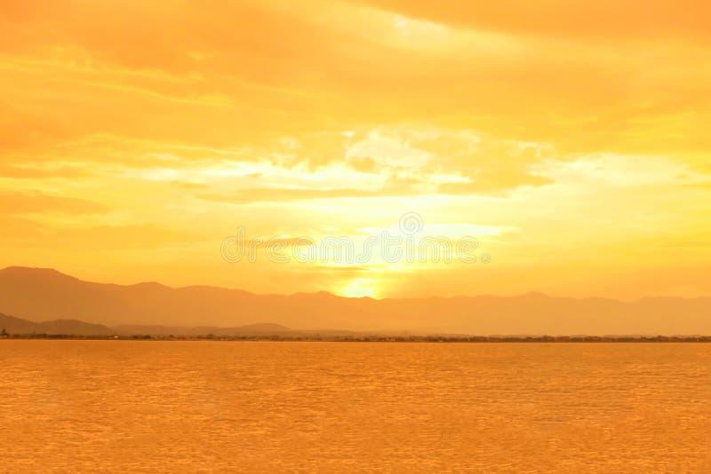 Solnedg?ng p? Phayao sj?n eller Kwan Phayao med det stora berget och moln Orange himmel med solljusreflexioner med vatten i lagun arkivfoton