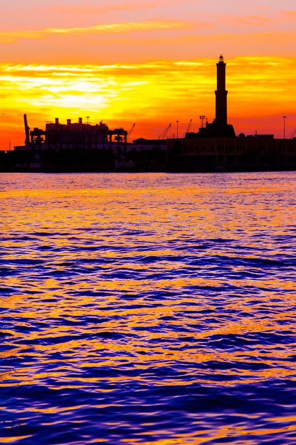 Solnedgång på port för Genua ` s, kontur av Lanternaen, Italien royaltyfri bild