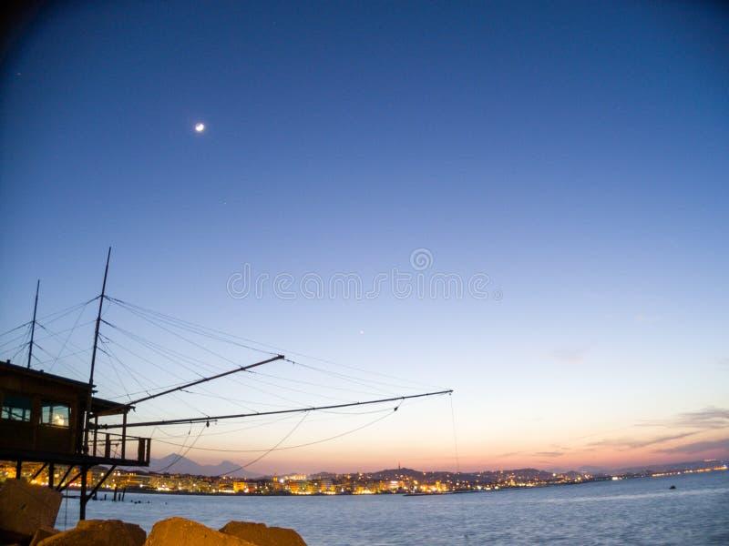 Solnedgång på porten av Pescara, med staden på sikt arkivfoto