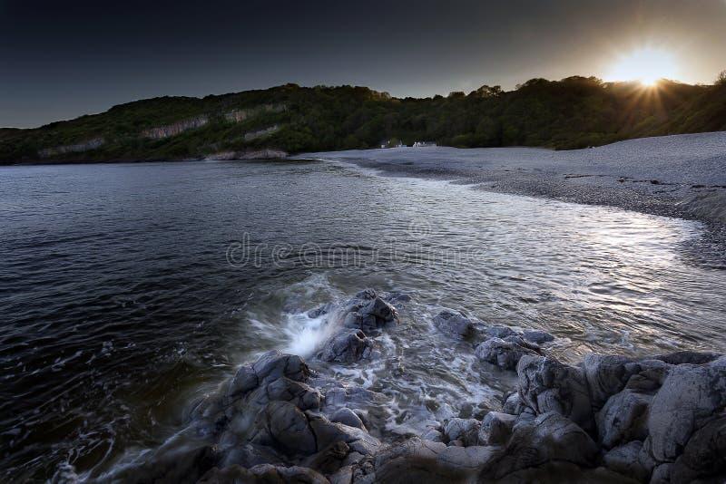 Solnedgång på Pwll Du Skälla arkivfoto