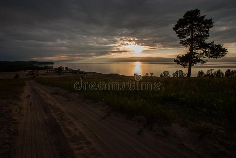 Solnedgång på sjön med ett träd och en sandig väg royaltyfria bilder