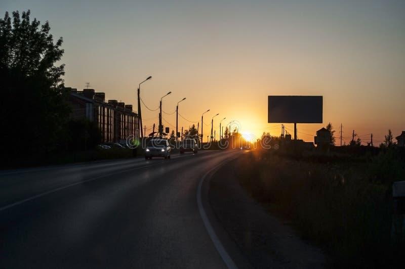 Solnedgång på stadsvägen med ljus på sidan av vägen och en affischtavla i sommaren royaltyfri bild