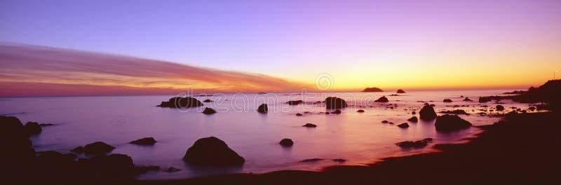 Solnedgång på stenig Stillahavs- shoreline fotografering för bildbyråer