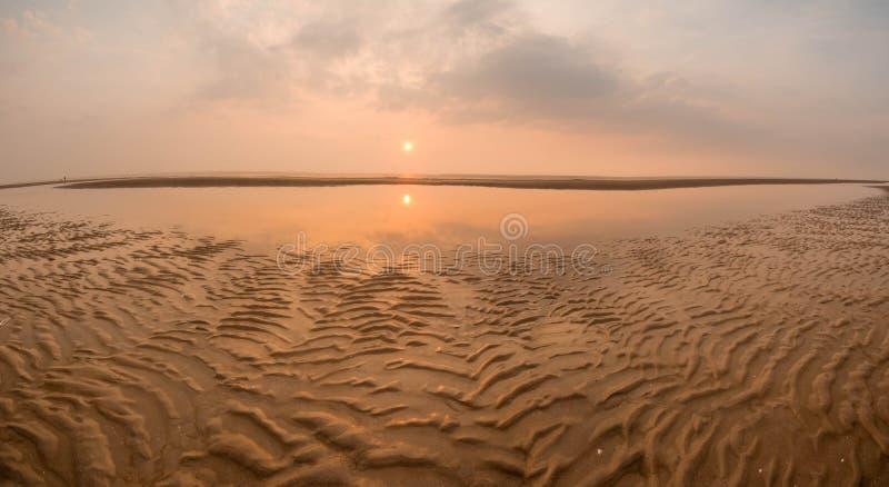 Solnedgång på stranden över ett inlands- hav royaltyfri bild