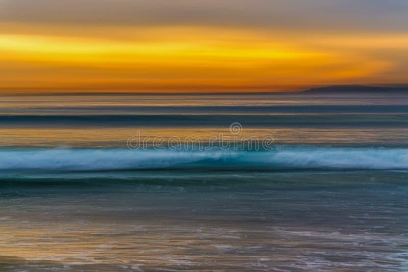 Solnedgång på stranden, havvågorna och den gula himlen royaltyfria bilder