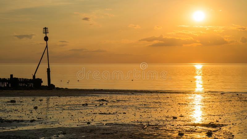 Solnedgång på stranden i Hunstanton, Norfolk, UK royaltyfri foto