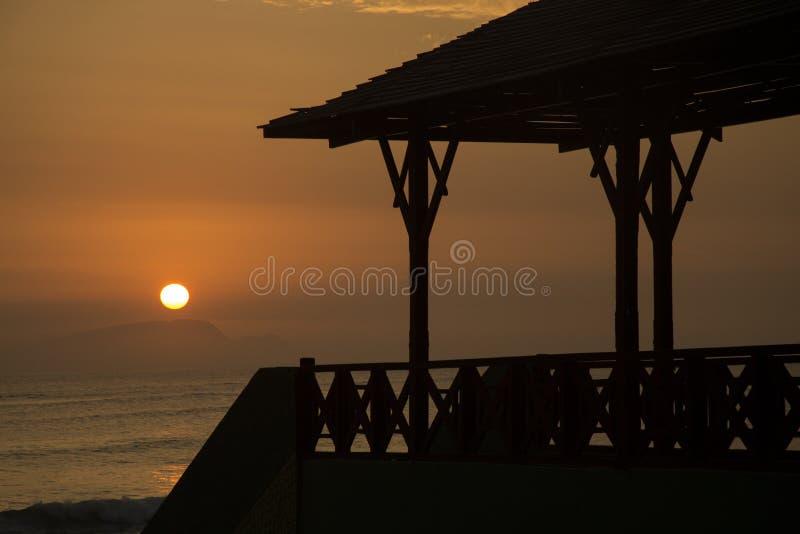 Solnedgång på stranden med bron royaltyfri bild