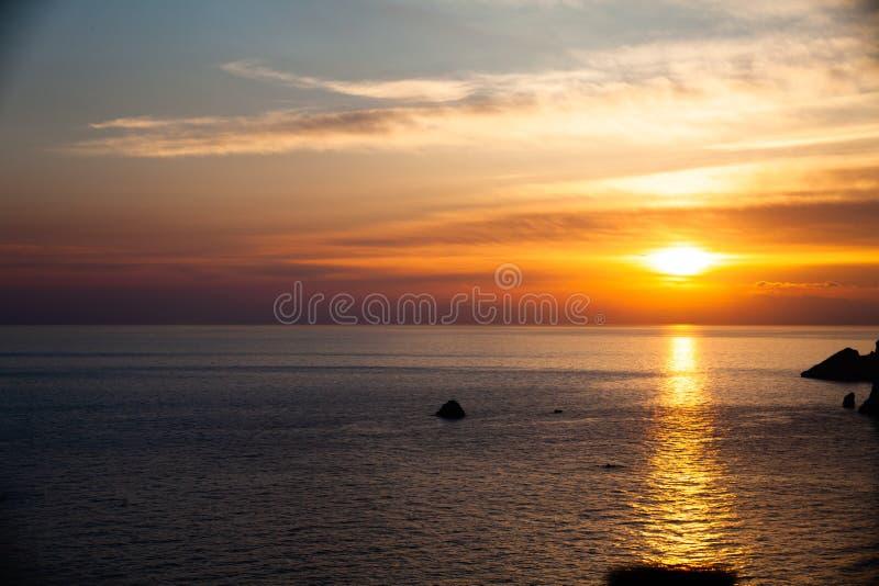 Solnedgång på stranden med moln Vatten för lugna hav Härliga färger i himlen Blåa och orange skuggor placera sig quiet avslappnan royaltyfri bild