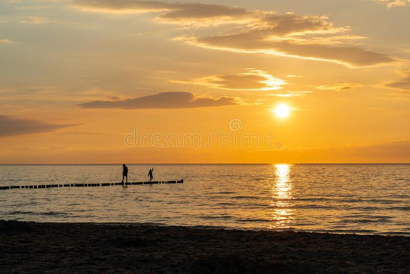 Solnedgång på stranden med två personer som svarta konturer i förgrunden royaltyfri fotografi