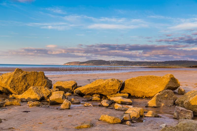 Solnedgång på stranden, Wales, UK royaltyfri bild