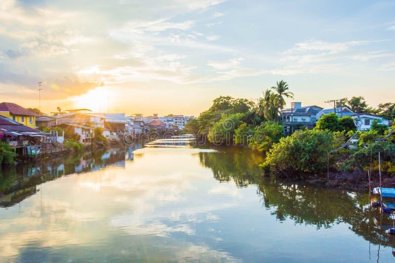 Solnedgång på thai hus bredvid floden royaltyfria bilder