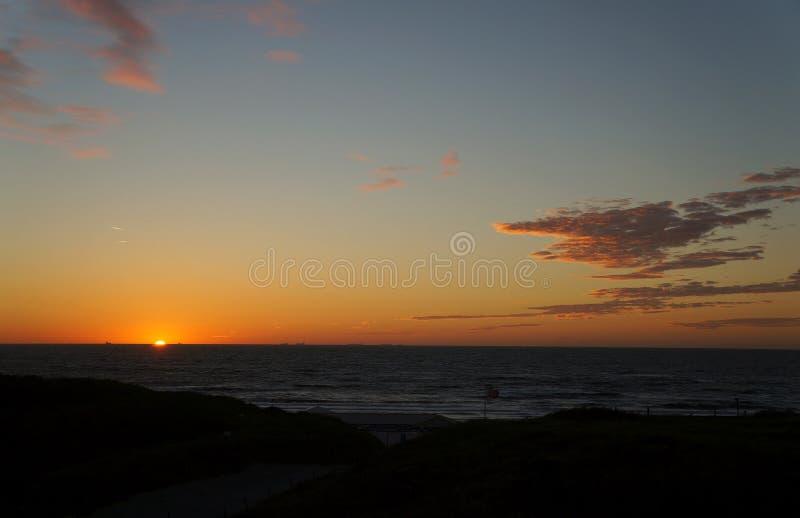 Solnedgång på Wijk den aan Zee stranden arkivfoton