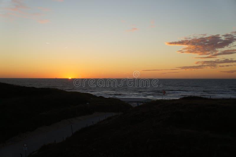 Solnedgång på Wijk den aan Zee stranden royaltyfri foto