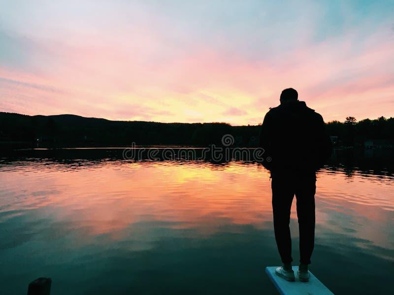 Solnedgång sjöreflexion arkivfoto