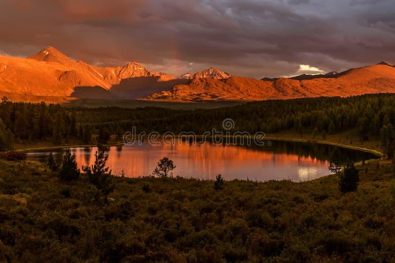 Solnedgång skogen för sjöberg fördunklar regnbågen arkivbilder