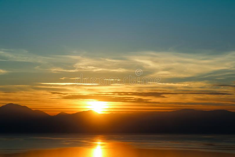 Solnedgång-solen ställer in bak bergen och över vatten med reflexion royaltyfri bild