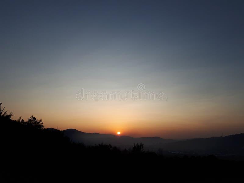 solnedg?ng solstr?lar som passerar till och med molnen, sk?nheten av berg och moln arkivbild