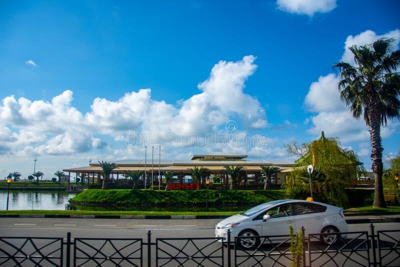 Solnedgång som är restourant med den härliga trädgården bredvid vägen i staden av Batumi arkivfoto