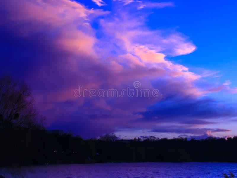 Solnedgång som färgar molnen i bygden arkivfoto