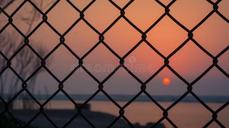 Solnedgång som fångas till och med staketet royaltyfria bilder