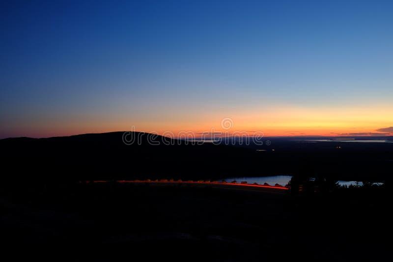 Solnedgång som förbiser det Cadillac berget i Maine med trafik som förbi gör strimmig arkivbild