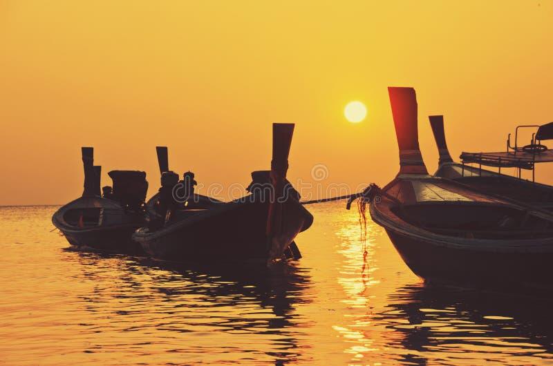 Solnedgång som fiskar thailändskt trä, longtailfartyg arkivfoton