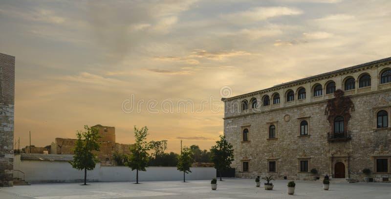 Solnedgång som ses från borggården av slotten för ärkebiskop` s i Alcala de Henares, Spanien, sikt av den huvudsakliga fasaden royaltyfri foto