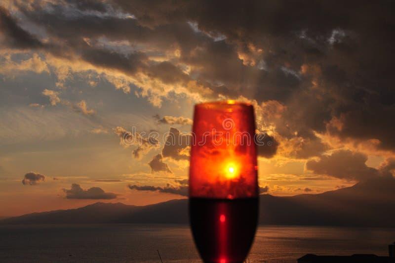 Solnedgång som ses från exponeringsglaset av rött vin arkivbild