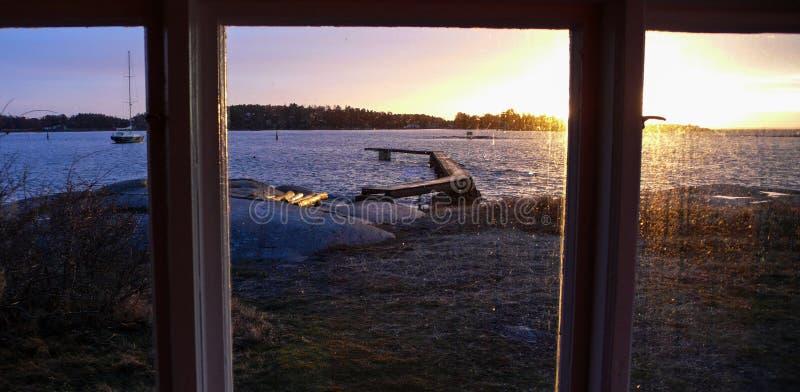 Solnedgång som ses till och med ett fönster arkivfoton