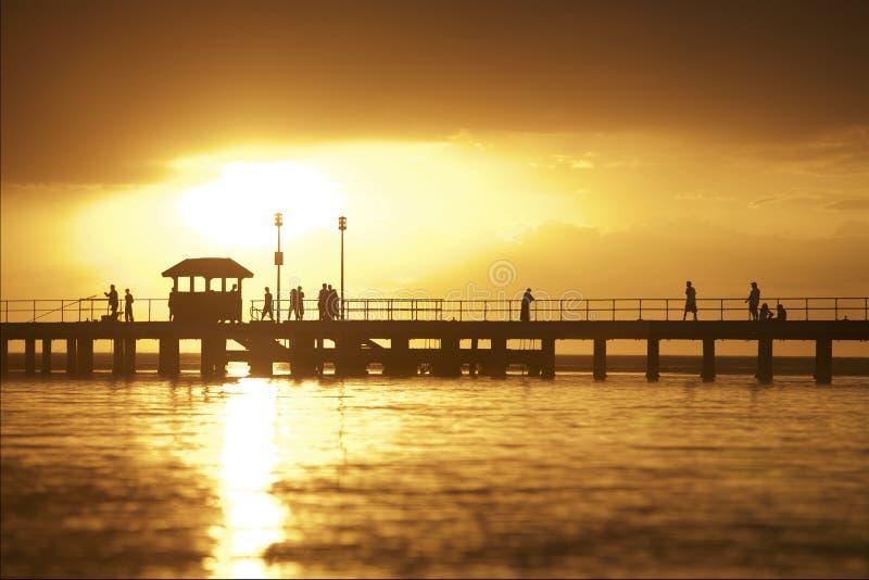 Solnedgång som ställer in över pir arkivbilder